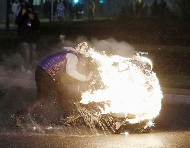 A man ignites a burning barricade as protesters clash with French riot police in Bobigny