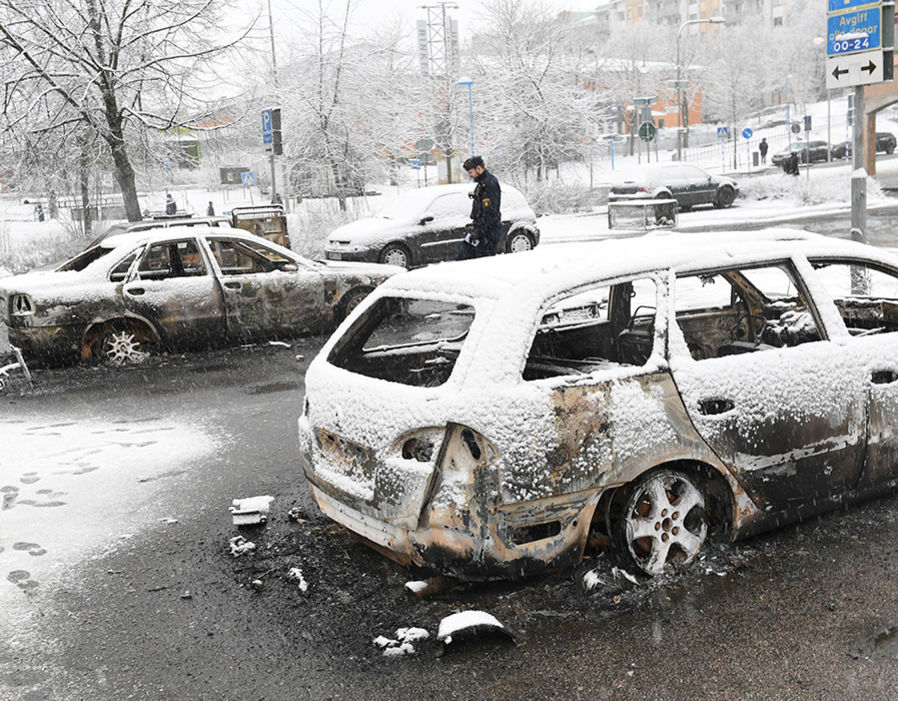 A policeman investigates a burnt car in the Rinkeby suburb outside Stockholm