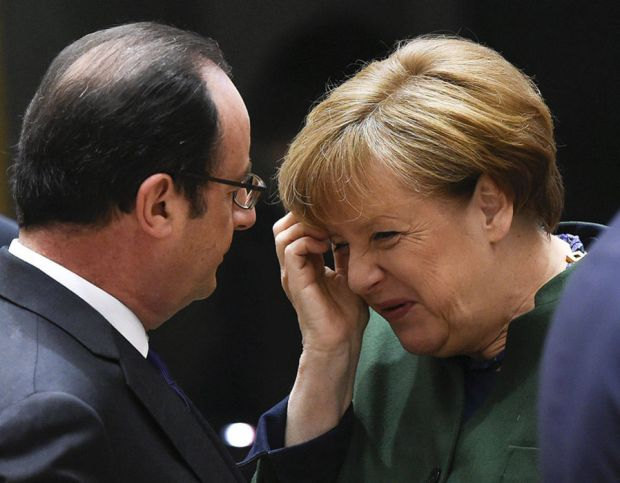 French President Francois Hollande speaks with German Chancellor Angela Merkel on the second day of a European Summit at the Europa Building at the EU headquarters in Brussels