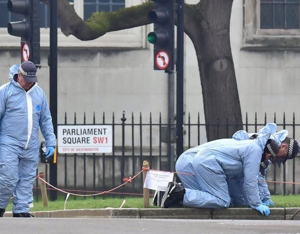 Police forensic officers in Parliament Square outside the Houses of Parliament in London, after seven people were arrested in raids in London, Birmingham and elsewhere linked to the Westminster terror attack