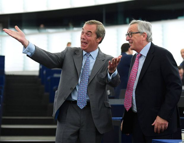Former leader of the UK Independence Party (UKIP) Nigel Farage (L) gestures as he speaks with EU Commission president Jean-Claude Juncker (R) prior to a debate on the conclusions of the last European Council, at the European Parliament in Strasbourg