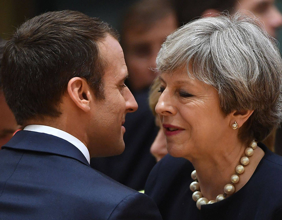 French President Emmanuel Macron greets British Prime Minister Theresa May as they attend an European Union leaders summit