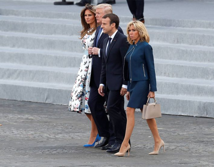 French President Emmanuel Macron, his wife Brigitte Macron, US President Donald Trump and First Lady Melania Trump walk on the Place de la Concorde at the end of the traditional Bastille Day military parade in Paris
