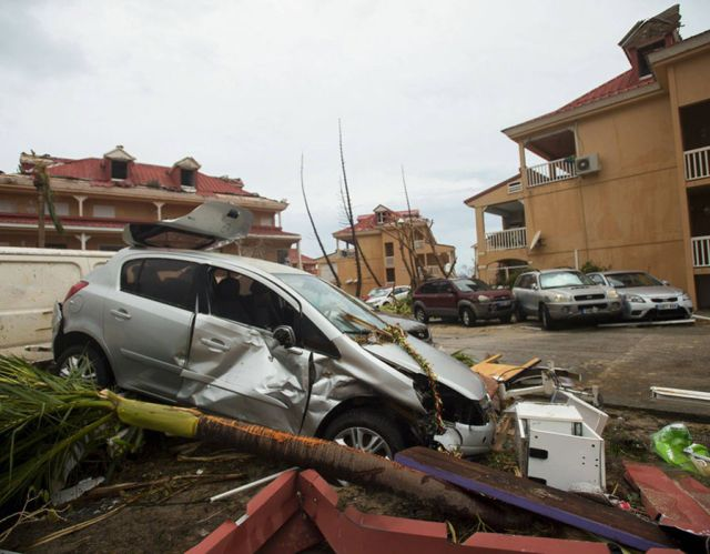 A damaged car and debris in Marigot after Hurricane Irma