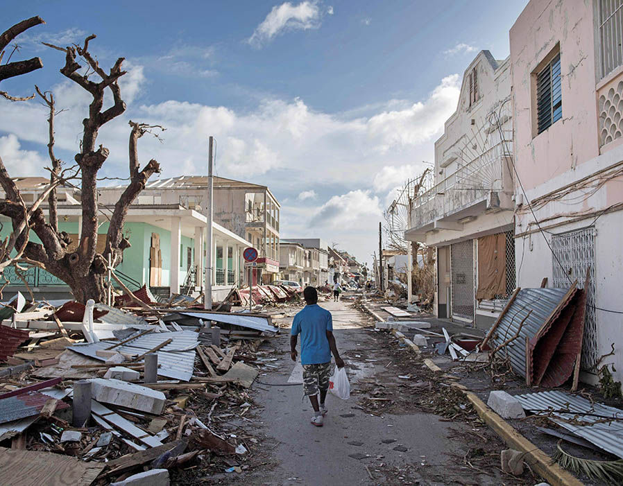 A man walks on a street covered in debris after hurricane Irma hurricane