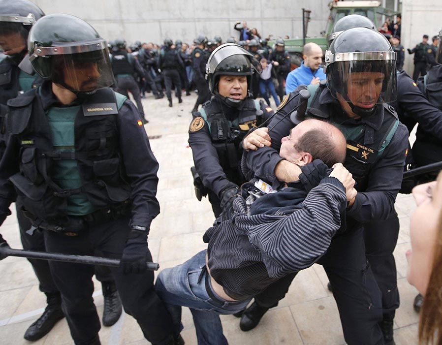 Spanish Guardia Civil guards drag a man