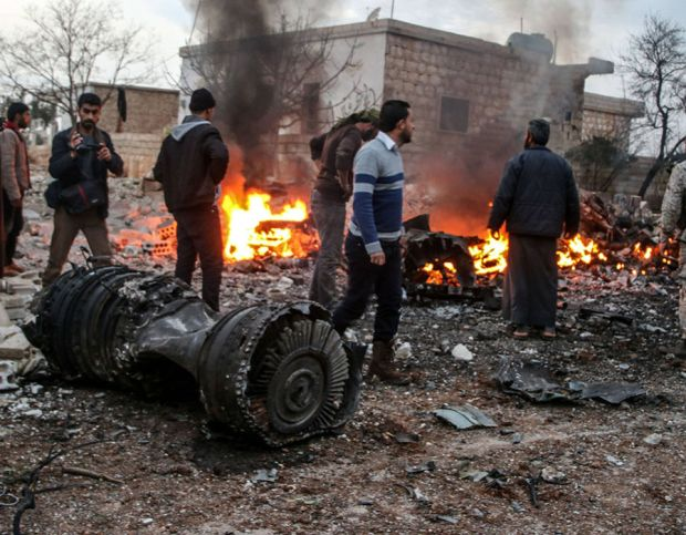 People walk amidst the rubble of the Russian Sukhoi Su-25 fighter jet scattered on the ground