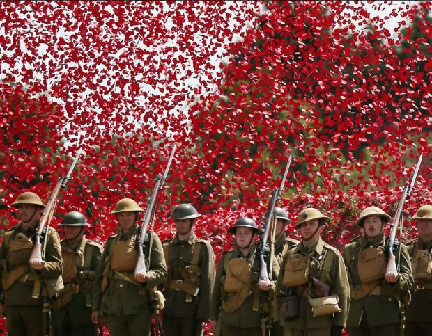 soldiers stand under a shower of a million poppy flowers