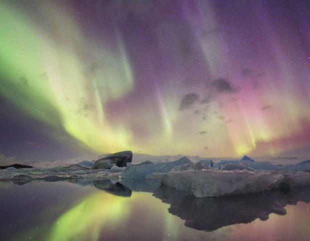 Aurora lights reflect in lagoon, Jokulsarlon, Iceland