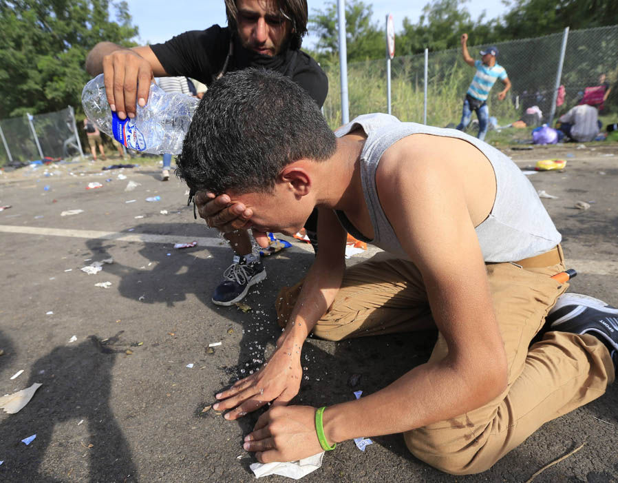 A Migrant is helped to wash tear gas from his eyes after clashes with Hungarian police at the Horgos border