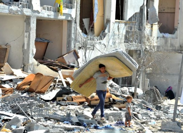 A Palestinian man salvages items from the rubble of his home destroyed by Israeli strikes on a building in northern Gaza Strip. Aug 7, 2014. Credit: UN Photo/Shareef Sarhan