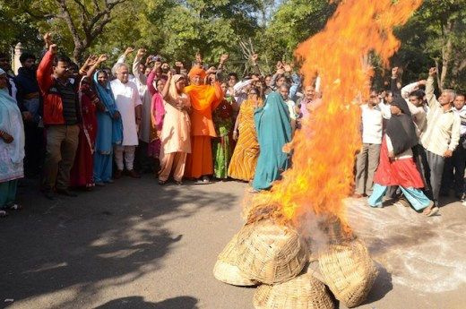 At a rally in New Delhi, Dalit women burn baskets used to collect human waste as a sign of protest against the caste-based practice of 'manual scavenging'. Credit: Shai Venkatraman/IPS