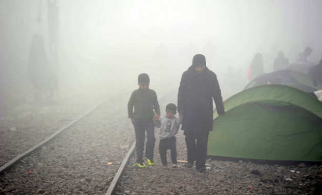 In March 2016, a mother walks through misty weather with her two sons along train tracks in Idomeni, Greece. Credit: ©UNICEF/UN012794/Georgie