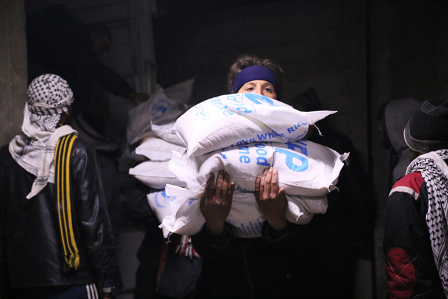 In Madaya, Syria, local community members help offload and distribute humanitarian aid supplies. Photo: WFP/Hussam Al Saleh
