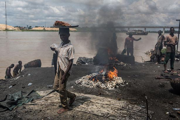 On 24 October 2016 in Yenagoa, Bayelsa State, Nigeria, children pass in front of a flame fed by waste and rubber materials in order to make Kanda, a type of smoked meat, at an abattoir. Photo: UNICEF/Tanya Bindra