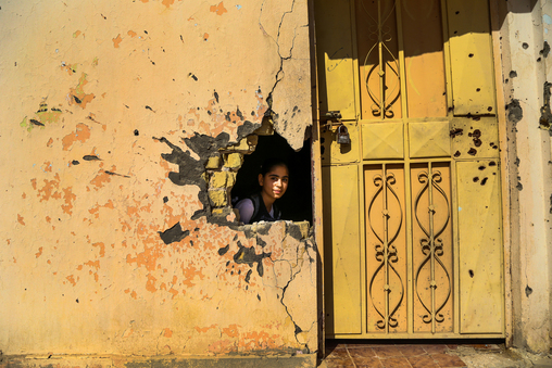 Iraq 2016: A girl looks out through a hole in a wall at a damaged school in Ramadi, in Anbar Governorate – which has been especially hard hit by conflict, violence and internal displacement. Some 3.3 million people in the country are currently displaced and over 10 million are in need of humanitarian assistance as a result of the country's ongoing crisis. About 1 million school-aged Iraqi children are internally displaced; 70 per cent of them have missed an entire year of education. © UNICEF/UN/Khouzali