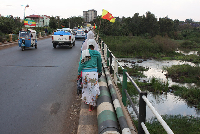 Ethiopian national flags and regional Amhara flags flutter along the bridge over the Blue Nile on the road going east from Bahir Dar that the protesters took last year. Credit: James Jeffrey/IPS