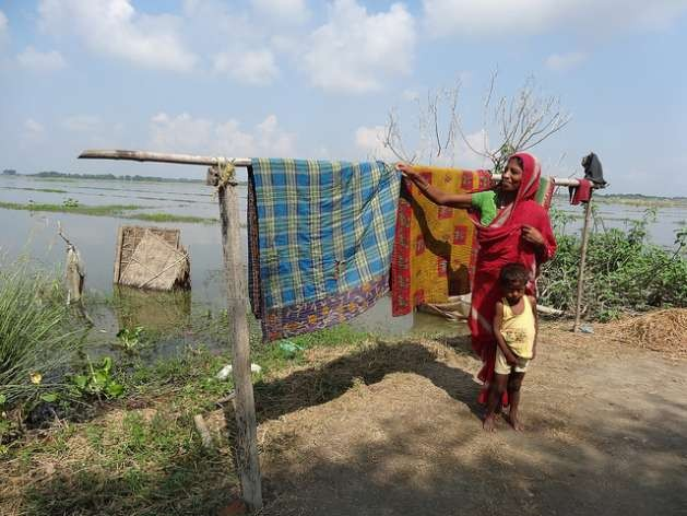 A woman dries blankets after her home went underwater for five days in one of the villages of the Morigaon district, India. Credit: Priyanka Borpujari/IPS