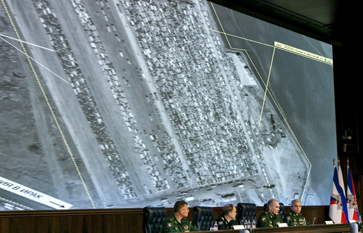 Russian top military officials speaking to the media in front of an aerial image of oil trucks near Turkey's border with Syria