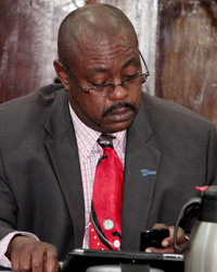 Minister Of National Mobilisation, Frederick Stephenson Uses Handheld Devices In Parliament On Friday.