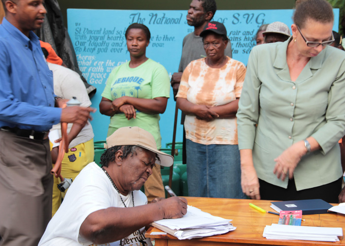 Rita Charles Signs Her Name As She Receives A Fridge In Spring Village On Wednesday. (Iwn Photo)
