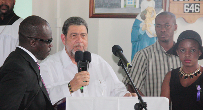Prime Minister Gonsalves Is Flanked By Two Of Lynch'S Children, Ken, Left, And Shafia, Right, And A Member Of His Security Detail As He Speaks At The Funeral. (Iwn Photo)