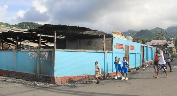 St. Mary'S Rc Student And Other Pedestrians Walk Past The Burnt Out Verbeke Centre On Monday Morning. (Iwn Photo)