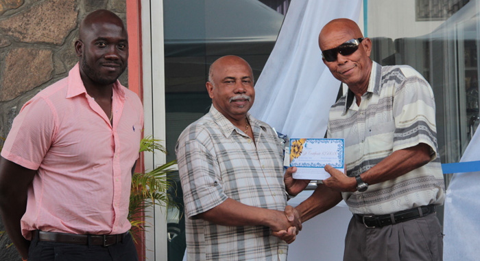 Sports Minister Cecil &Quot;Ces&Quot; Mckie, Centre, Presents The Award To Honouree Stanley &Quot;Gunny&Quot; Hinds, Right, As Kevin Dickson, Chair Of Coreas Pharmacy Council Looks On. (Iwn Photo)