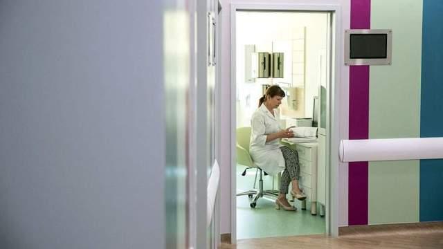 Женщина-врач в кабинете работает с документами