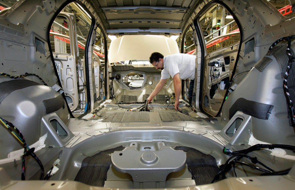 medium resolution of an auto worker puts a wiring harness into an empty vehicle body during production of general