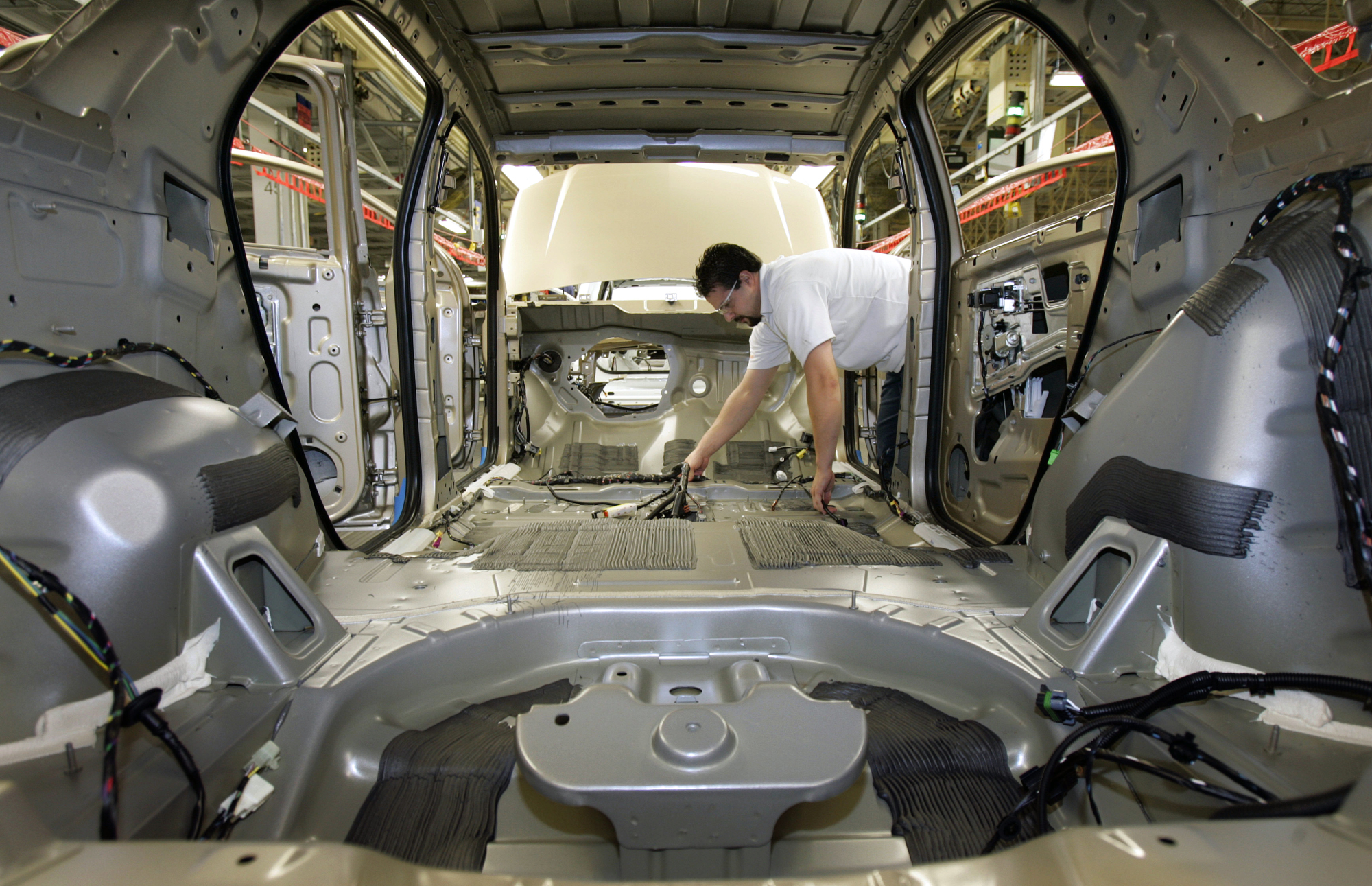 hight resolution of an auto worker puts a wiring harness into an empty vehicle body during production of general
