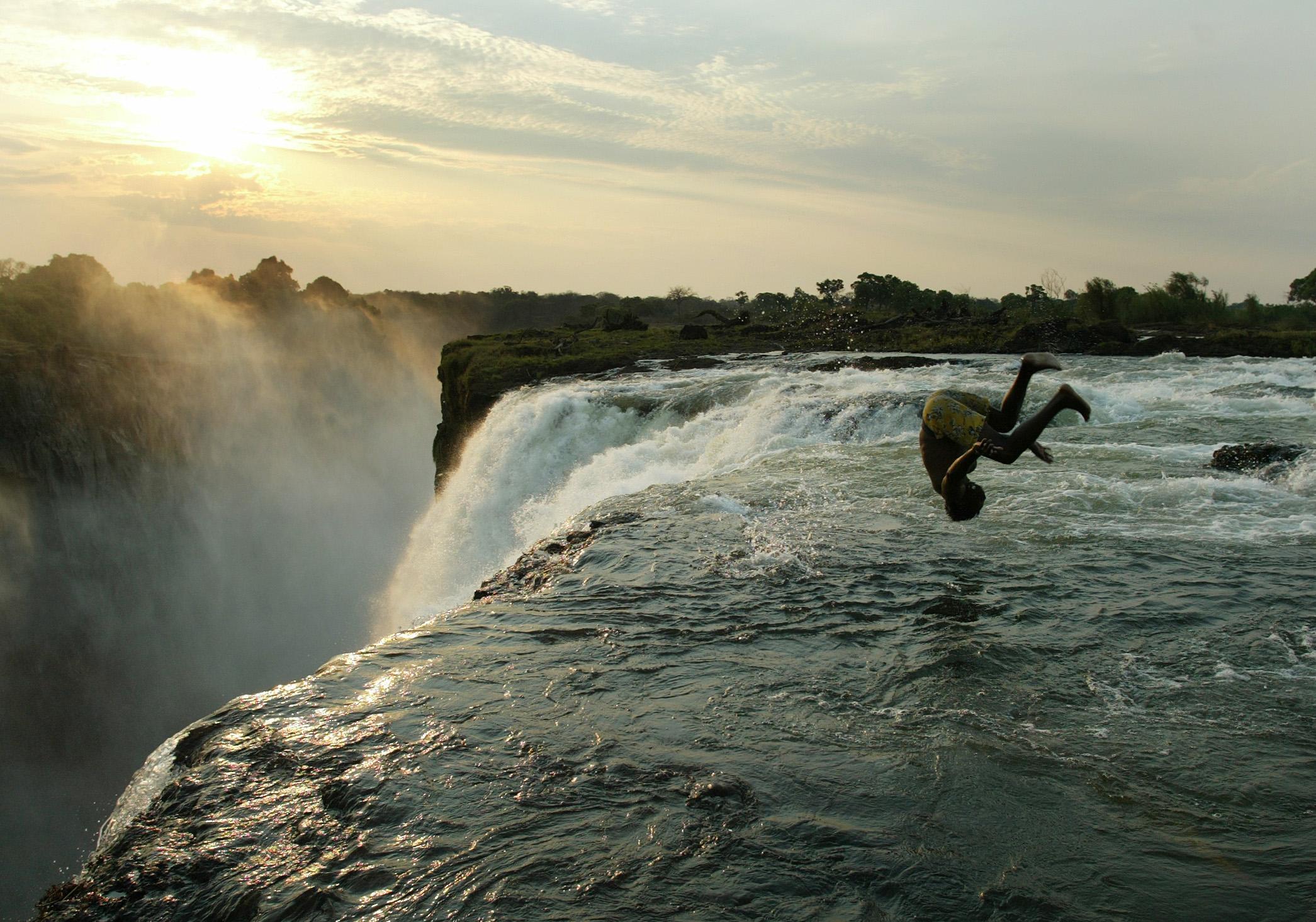 Zambian man somersaults into a pool at edge of Victoria Falls on the Zambezi River