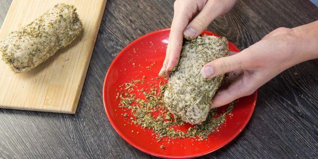 Снимите пергамент и фольгу и обваляйте колбасу в травах