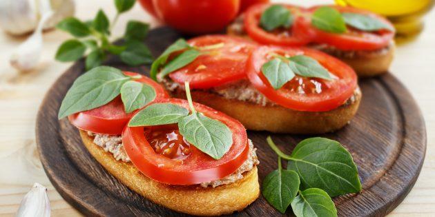 タラの肝臓とトマトのお祝いのテーブルの上のサンドイッチ