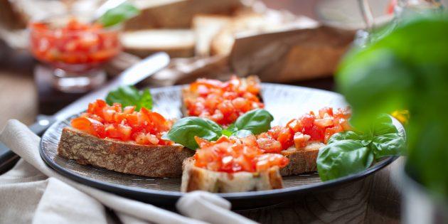 トマト、ブルガリアのコショウとバジルのお祝いテーブルのためのサンドイッチ