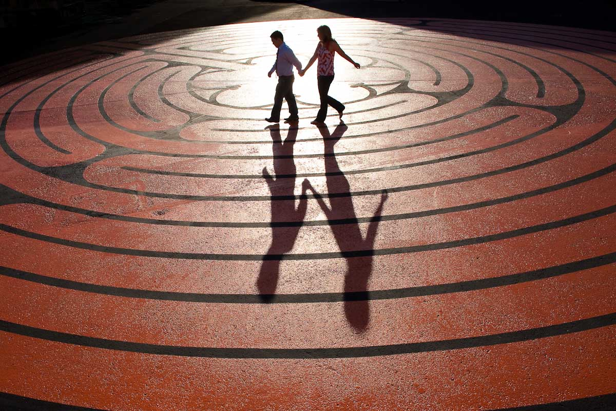 two individuals running across labyrinth leaving a shadow behind