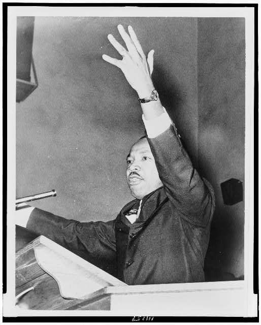 [Martin Luther King, Jr., half-length portrait, facing left, with left arm raised, at freedom rally, Washington Temple Church]