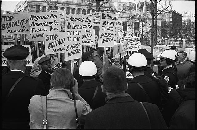 [African American demonstrators outside the White House, with signs