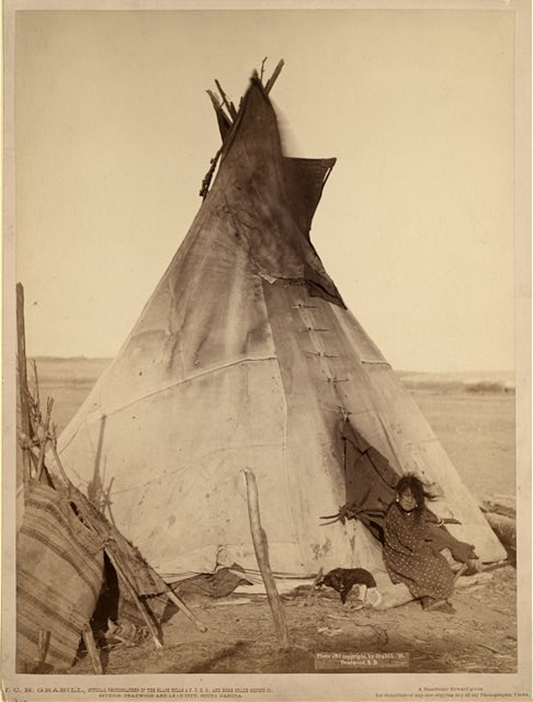 [A young Oglala girl sitting in front of a tipi, with a puppy beside her, probably on or near Pine Ridge Reservation]