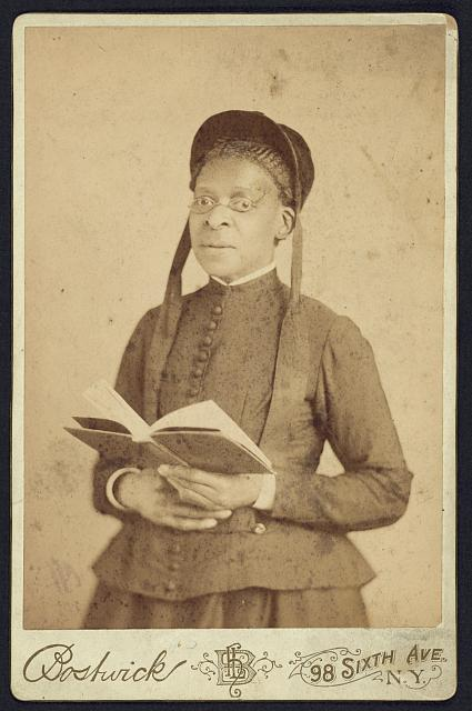 [Three-quarter length portrait of an African American woman posed with book]