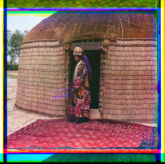 [Full-length profile portrait of a woman, possibly Turkman or Kirgiz, standing on a carpet at the entrance to a yurt, dressed in traditional clothing and jewelry]