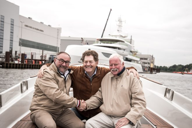 Hans Schaedla, Andrew Winch of Winch Design, and Captain Ray Shore are all smiles in front of Excellence in Lemwerder