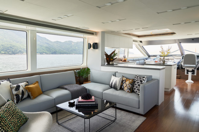 Lit by big windows, the saloon features a lounge and, forward, a large L-shaped kitchen with an island counter, a corner dining table and a single-seat helm station