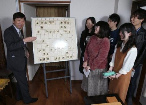 学生記者の前で将棋の駒を動かす杉本昌隆七段(左)=名古屋市北区で、兵藤公治撮影