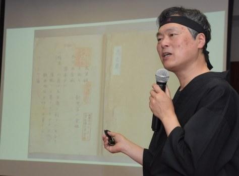 発見された忍術書の写真(奥)を示しながら説明する清川繁人教授=青森大で2018年7月4日午後1時半、一宮俊介撮影
