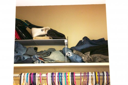 A Tiny Apartment S Cluttered Unorganized Bedroom Closet With Jeans Tered On Shelf