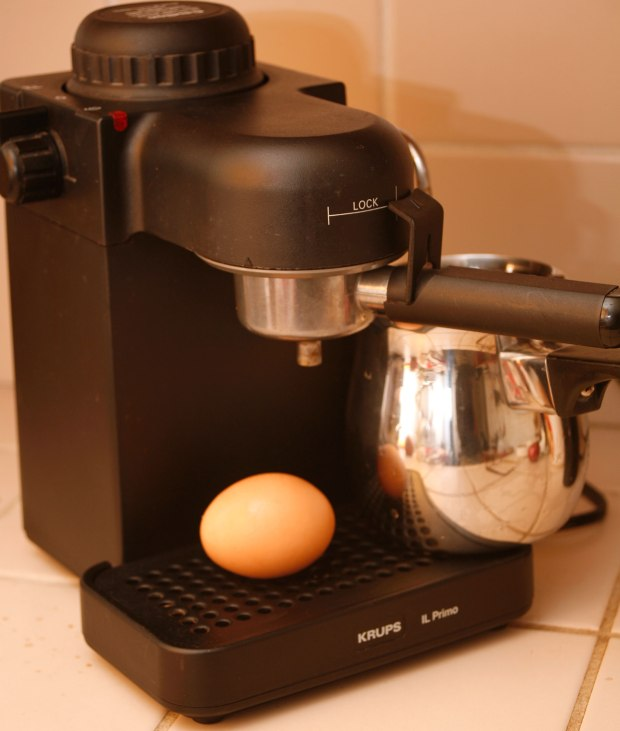 uncracked egg sitting on heating plate of espresso machine