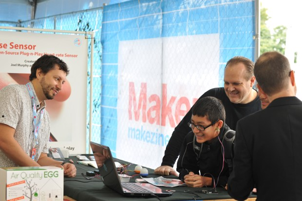 Michael, on his third visit to the Maker Faire, tests the Pulse Sensor designed by Yuri Gitman (l) and Joel Murphy (far r). (Gregory Hayes / MAKE)