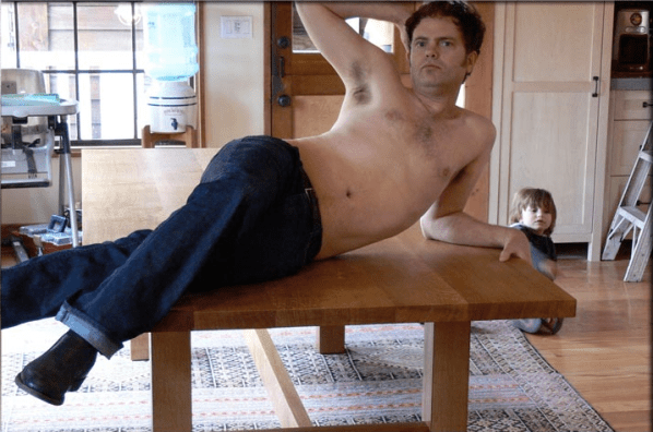 Nick Offerman's friend and fellow comedic actor Rainn Wilson posing atop one of Offerman's tables.