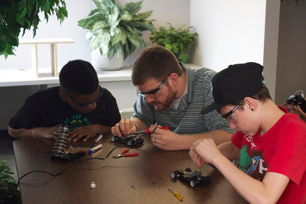 Andrew working with Owen and Breshawn on soldering the pins.